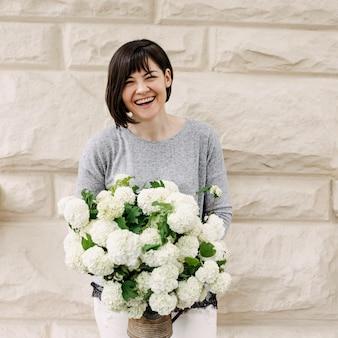 Vrolijke vrouw met een emmer met hortensiabloemen