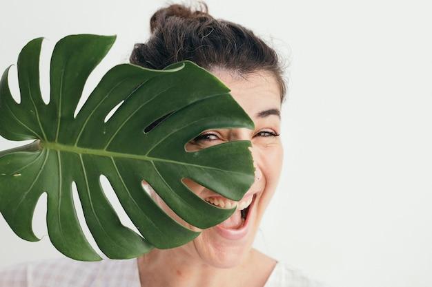 Vrolijke vrouw met een gespleten blad philodendron