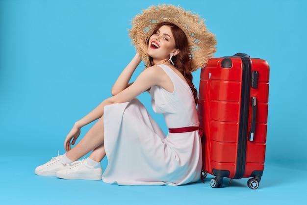 Vrolijke vrouw met een hoed zit op de vloer met een reisbestemming voor een koffer