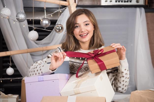 Vrolijke vrouw met een kerstcadeau in de woonkamer.