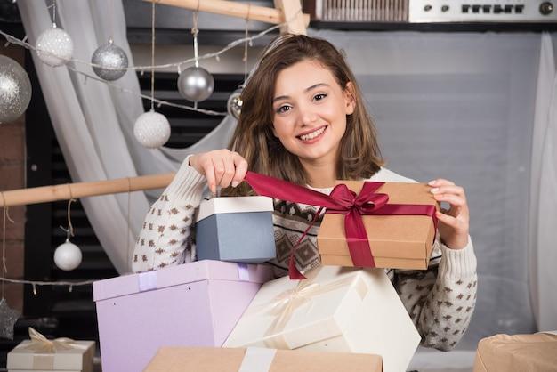 Vrolijke vrouw met een kerstcadeau in de woonkamer. Gratis Foto