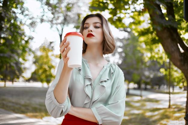 Vrolijke vrouw met een kopje koffie in het park in de vrijetijdslevensstijl van de straat