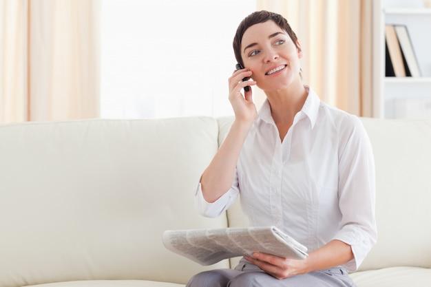 Vrolijke vrouw met een mobiel en een krant