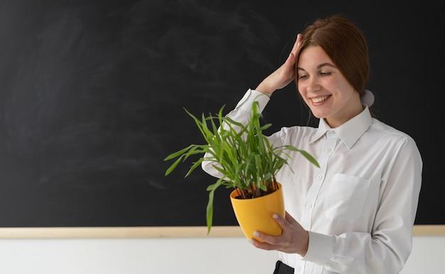 Vrolijke vrouw met een plant in de buurt van een schoolbord