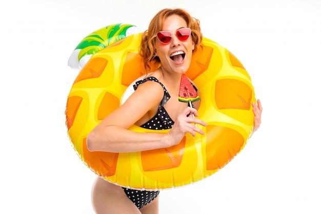 Vrolijke vrouw met eerlijk rood haar in zwempak, beeld dat op wit wordt geïsoleerd