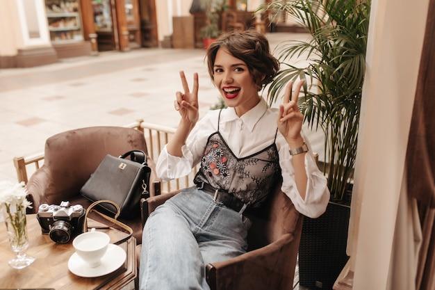 Vrolijke vrouw met felle lippenstift in spijkerbroek met riem vredestekens in café. koele vrouw met kort haar in wit overhemd glimlacht in restaurant.