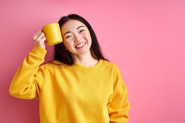 Vrolijke vrouw met gele mok in handen glimlachen, gelukkig begin van de dag hebben. geïsoleerde roze achtergrond