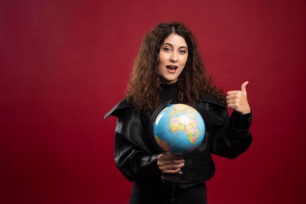 Vrolijke vrouw met globe en duimen opgevend.