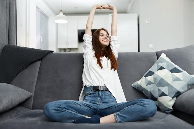 Vrolijke vrouw met haar handen boven haar hoofd zittend op de bank, comfortabel zittend in het appartement.