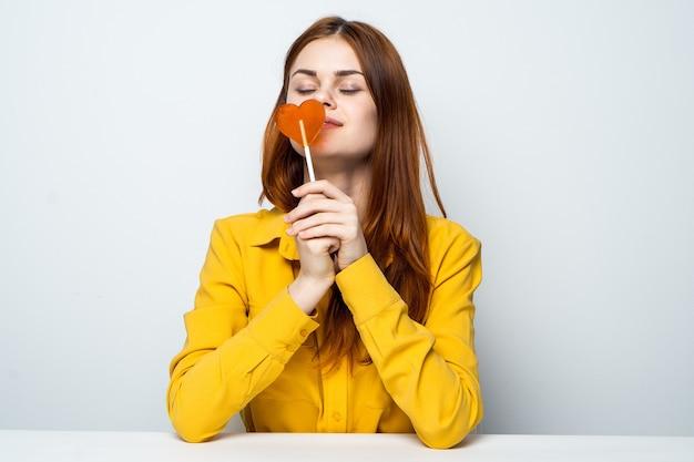 Vrolijke vrouw met hartvormige lolly zittend aan de tafel levensstijl