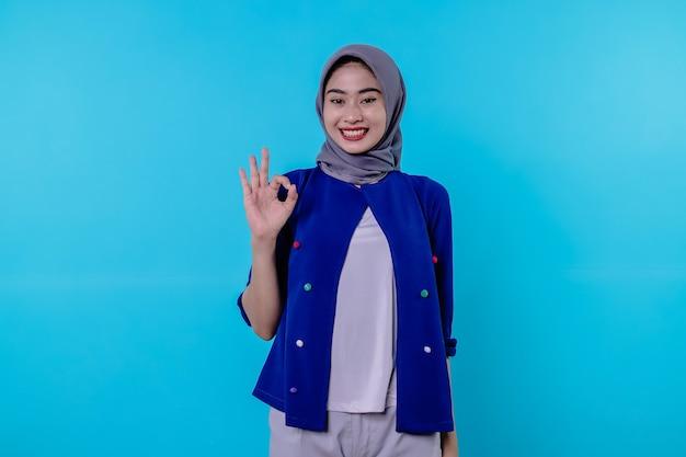Vrolijke vrouw met het dragen van hijab met een goed teken, glimlachen, ja zeggen, aanmoedigen om iets te kopen, een goed gebaar maken