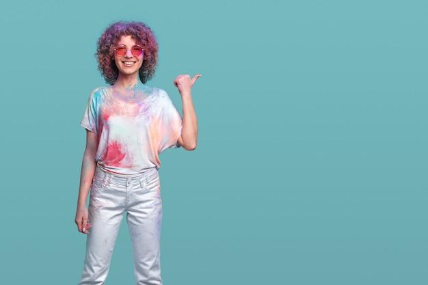 Vrolijke vrouw met holi-kleuren die opzij wijzen
