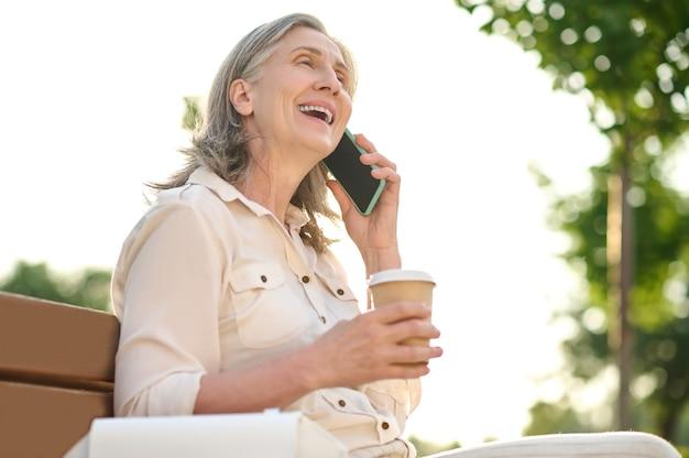 Vrolijke vrouw met koffie praten op smartphone