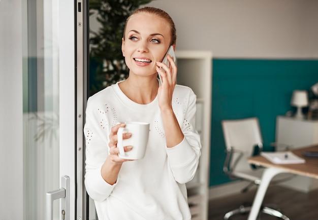Vrolijke vrouw met koffie praten via mobiele telefoon