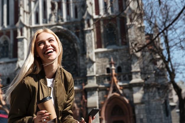 Vrolijke vrouw met kop van koffie en smartphone het lachen