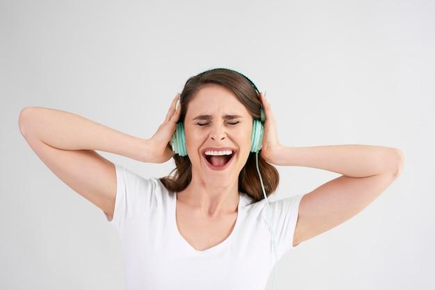 Vrolijke vrouw met koptelefoon luisteren naar muziek