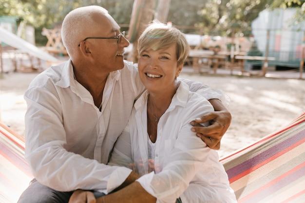 Vrolijke vrouw met kort blond kapsel in witte kleren, zittend op een hangmat en knuffelen met lachende man in brillen op strand.