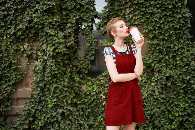 Vrolijke vrouw met kort haar buiten een kopje met een drankje zomervakantie