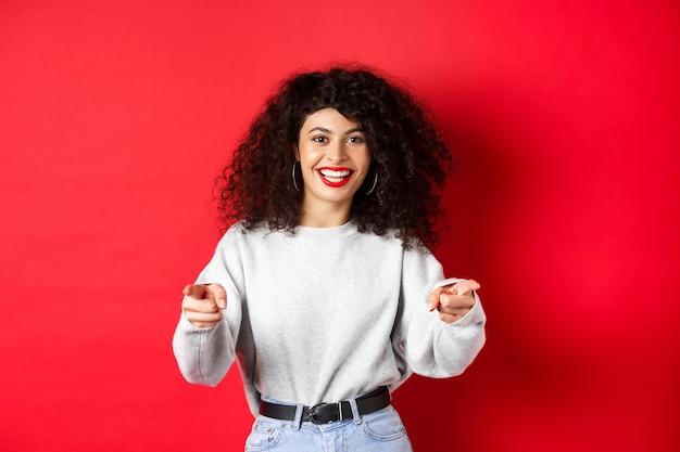 Vrolijke vrouw met krullend haar die je uitnodigt om nieuwelingen te rekruteren die met de vingers naar de camera wijzen en lachen...