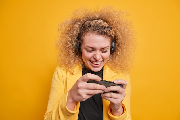 Vrolijke vrouw met krullend haar verslaafd aan videogames speelt op mobiele telefoon maakt gebruik van draadloze hoofdtelefoons geconcentreerd op display geniet van gamen, formeel gekleed geïsoleerd over levendige gele muur