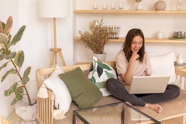 Vrolijke vrouw met laptop op de bank