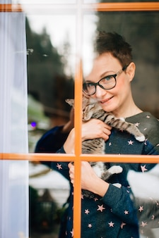 Vrolijke vrouw met mooi gezicht heeft een mooie kat op haar handen en kijkt door raam