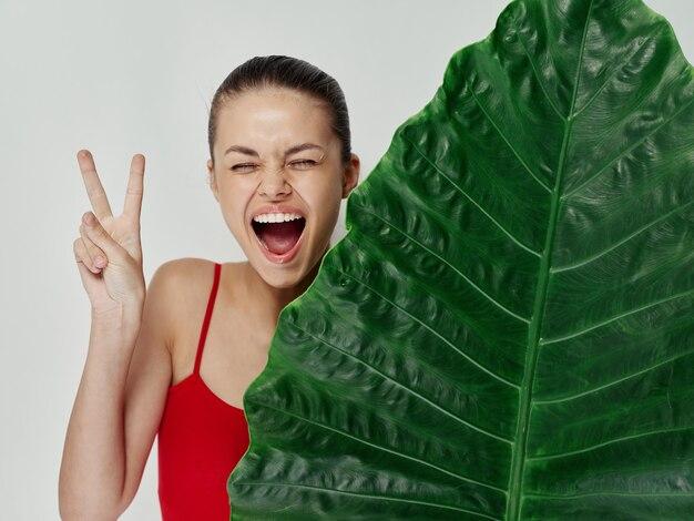 Vrolijke vrouw met open mond positief handgebaar palmblad rood zwempak
