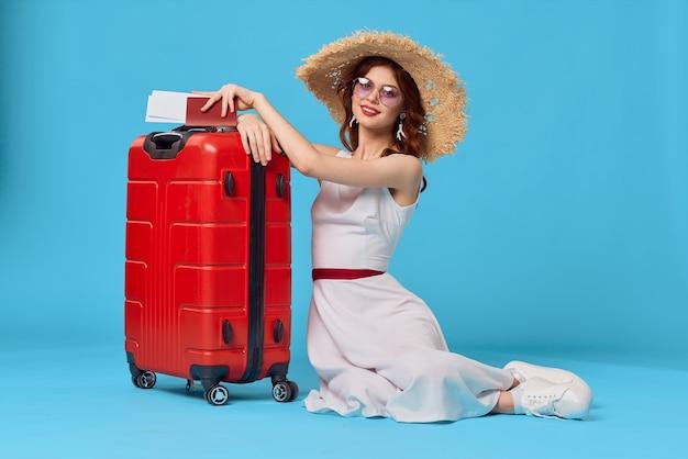 Vrolijke vrouw met rode koffer zittend op de vloer emoties geïsoleerde achtergrond