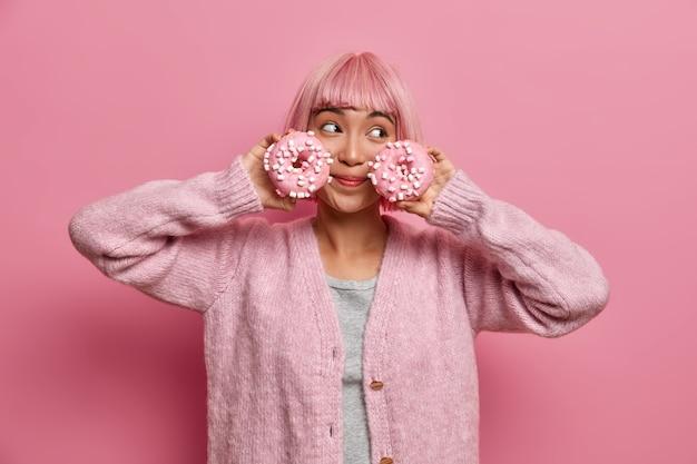 Vrolijke vrouw met roze kapsel, houdt twee geglazuurde donuts, poses