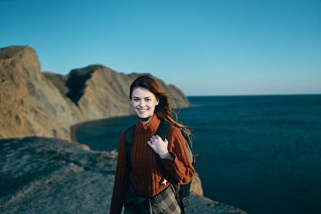 Vrolijke vrouw met rugzak op de horizon van aard rotsachtige bergen