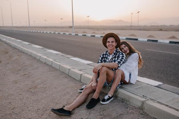 Vrolijke vrouw met schattig kapsel zittend op de weg, ineengedoken tegen haar vriendje in trendy hoed en lachen. charmante jonge vrouw en man rusten in de buurt van de snelweg na de reis en geniet van zonsondergang.
