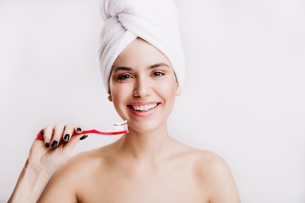 Vrolijke vrouw met schone huid lacht op geïsoleerde muur. dame met handdoek over haar hoofd gaat haar tanden poetsen.