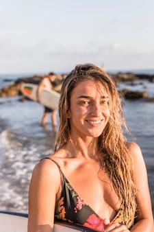 Vrolijke vrouw met surfplank die zich dichtbij overzees bevindt
