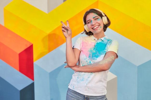 Vrolijke vrouw met verf op gezicht en kleren die vredesteken tonen