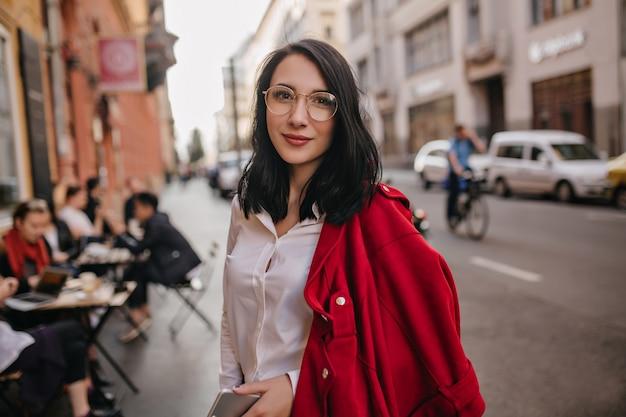 Vrolijke vrouw met vermoeide glimlach die zich voordeed op stadsmuur