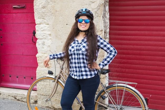 Vrolijke vrouw met zonnebril en helm op de muur rode deur en fiets