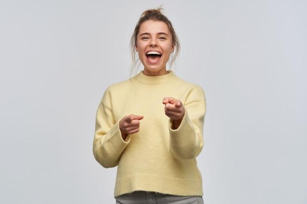 Vrolijke vrouw, mooi meisje met blond haar verzameld in een broodje. gele trui dragen. lachend van jou. wijzend met de vingers en kijken naar de camera, geïsoleerd over witte muur