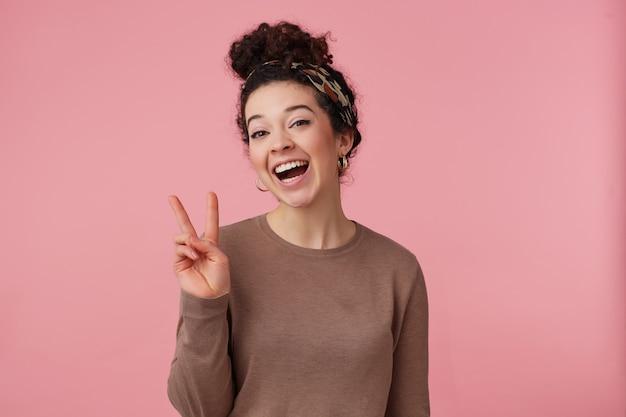 Vrolijke vrouw, mooi meisje met donker krullend haarbroodje. met hoofdband, oorbellen en bruine trui. heeft make-up. vredesteken tonen