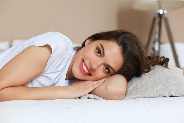 Vrolijke vrouw op bed lacht en kijkt naar de camera.