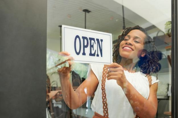 Vrolijke vrouw opening winkel