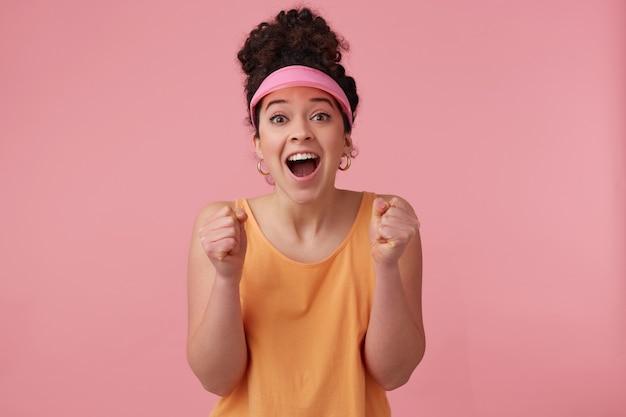 Vrolijke vrouw, positief meisje met donker krullend haarbroodje. het dragen van een roze klep, oorbellen en oranje tanktop. heeft make-up. bal je vuisten van opwinding