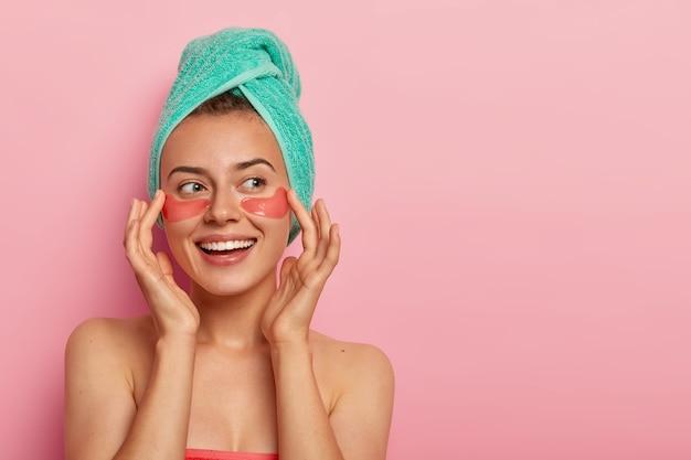 Vrolijke vrouw raakt zachtjes gezicht, lacht aangenaam, past hydrogelpleisters onder de ogen toe, staat naakt, heeft een gezonde huid