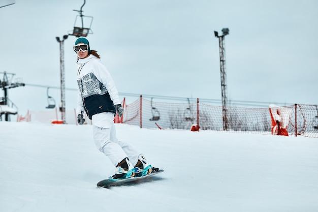 Vrolijke vrouw rijdt op snowboard in de bergen in de winter