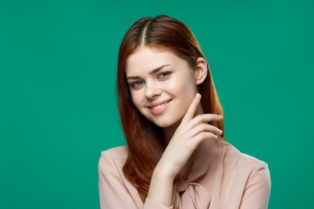 Vrolijke vrouw roze shirt emoties handgebaren close-up groene achtergrond