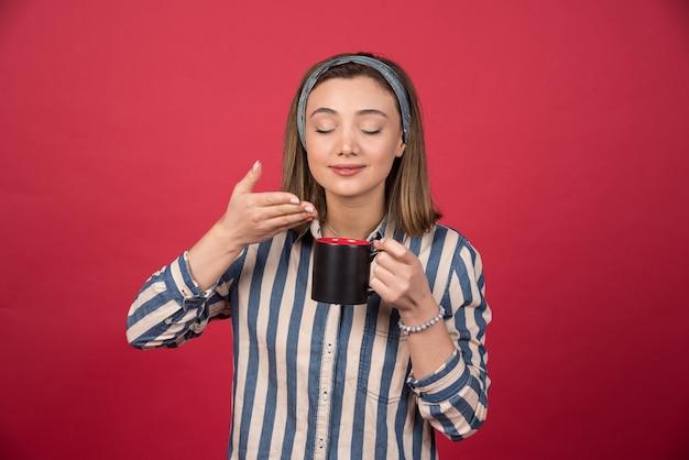 Vrolijke vrouw ruikt aroma van koffie op rode muur