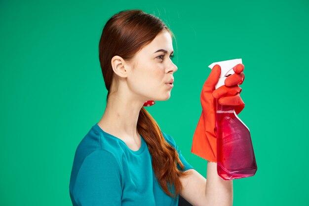 Vrolijke vrouw schoonmaakproducten thuiszorg werk groene achtergrond