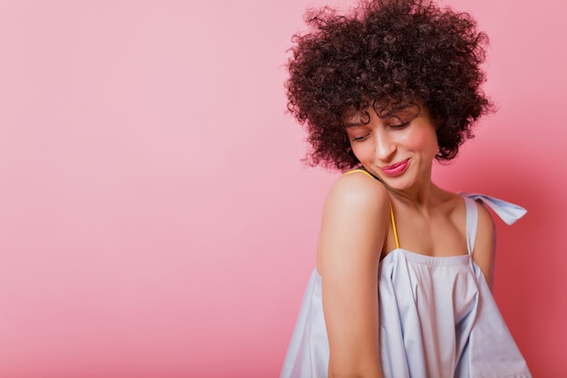 Vrolijke vrouw sloeg verlegen haar ogen neer en glimlachte op roze