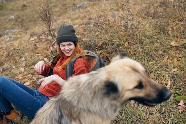 Vrolijke vrouw spelen met hond natuur reizen vriendschap