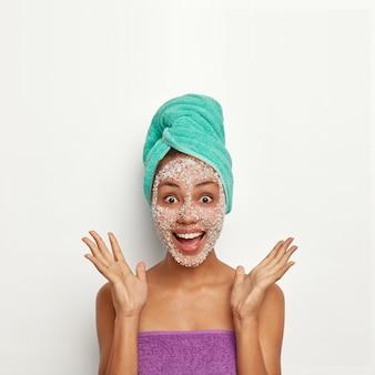 Vrolijke vrouw spreidt haar handpalmen, opent haar mond en voelt plezier, kijkt met afgeluisterde ogen, brengt peeling scrub aan op het gezicht, draagt een gewikkelde handdoek over het hoofd, krijgt verbazingwekkend nieuws