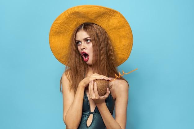 Vrolijke vrouw strand hoed exotische vruchten zwembroek levensstijl blauwe achtergrond